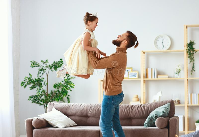 Happy father`s day! family dad and child daughter Princess dancing. At home stock photo