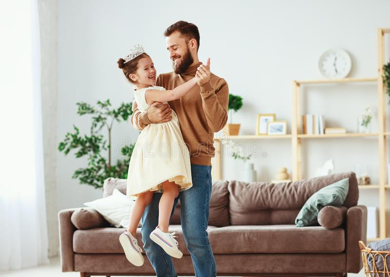 Happy father`s day! family dad and child daughter Princess dancing. At home stock images