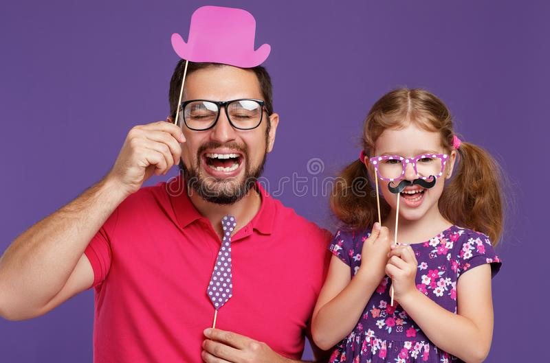 Happy father`s day! funny dad and daughter with mustache fooling royalty free stock photography