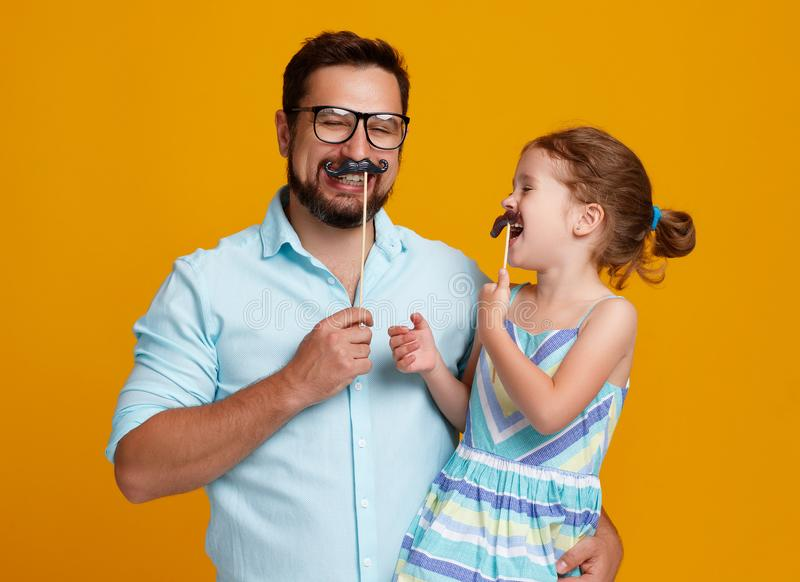 Happy father`s day! funny dad and daughter with mustache fooling stock photos