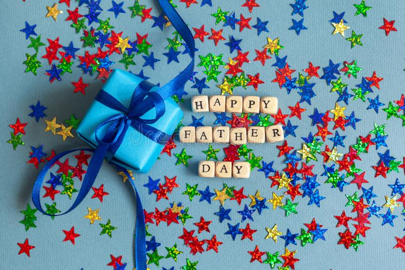 Happy Father`s day greeting card with decorated gift box on blue-gray background. Top view stock photography