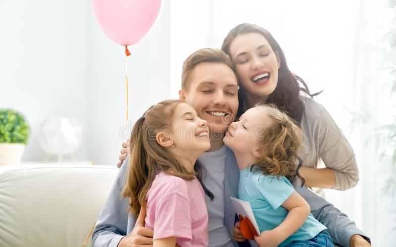 Happy father`s day. ! Children daughters and their mom are congratulating dad and giving him postcard. Daddy and girls smiling and hugging. Family holiday and royalty free stock photography