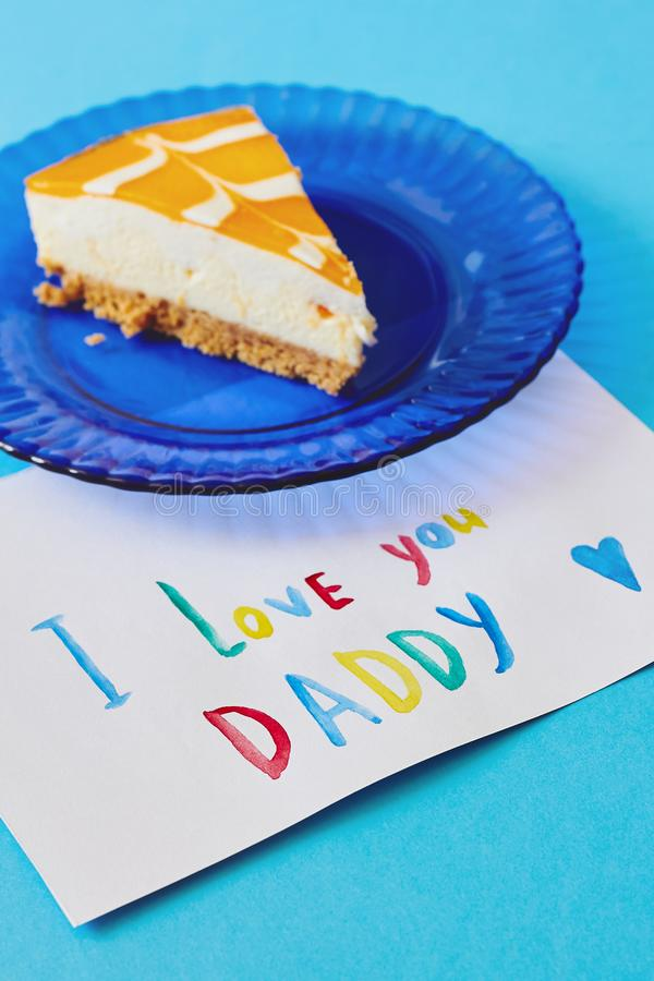Happy Father`s day, International Men`s day or Birthday card. Colored greeting card made by children and piece of cake on blue p. Happy Father`s day royalty free stock photography