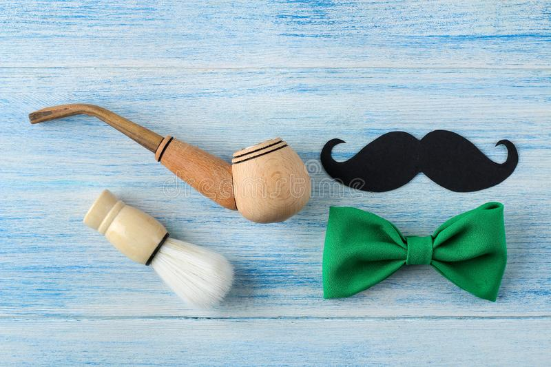 Happy father`s day. men`s decorative tie butterfly and smoking pipe on a light blue wooden background. top view stock image