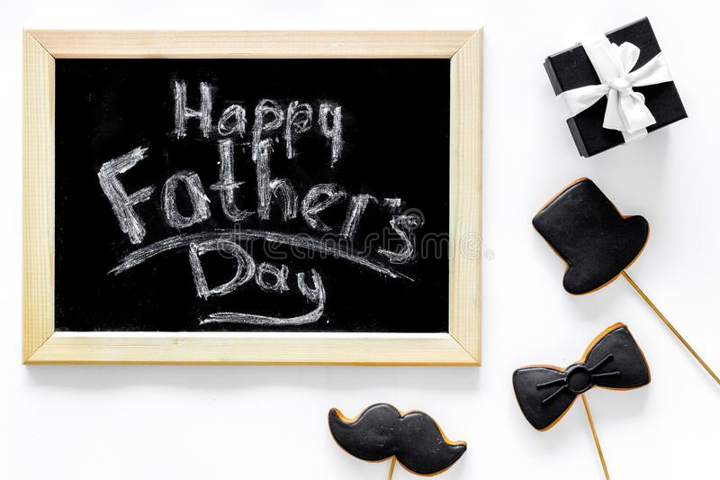 Happy father`s day morning with black tie, mustache and hat cookies, gift box for celebrate white background top view stock photos