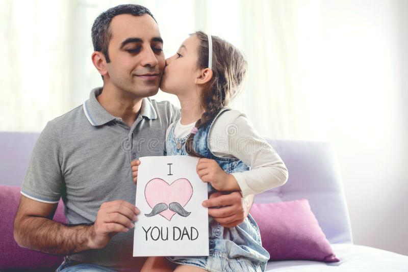 Happy Father`s Day Portrait. Child Daughter Kissing Her Smiling stock photo