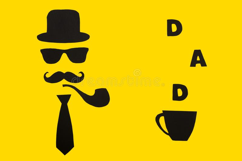 Happy Father`s Day.Postcard and a cup of hot coffee for dad.The hat, glasses, mustache, smoking pipe and bow tie on a yellow paper stock photo