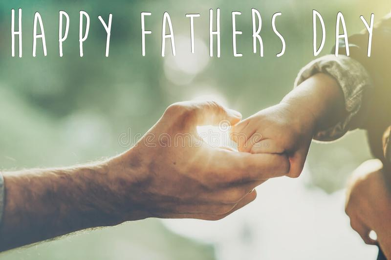 Happy father`s day text, greeting card concept. father and littl. E son holding hands in sunlight in summer forest. Trust, care and parenting family concept stock photo