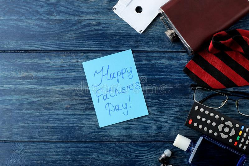 Happy father`s day. Text on paper and man`s tie, glasses and men`s accessories on a blue wooden table. men`s holiday. top view royalty free stock images