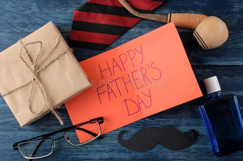 Happy father`s day. Text on paper and man`s tie, glasses and men`s accessories on a blue wooden table. men`s holiday. top view royalty free stock image
