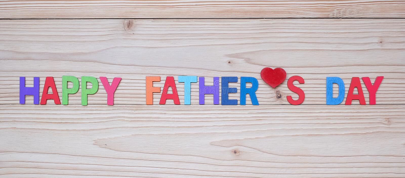 Happy Father`s Day text with red heart shape on wooden background. International Men`s Day concepts royalty free stock images