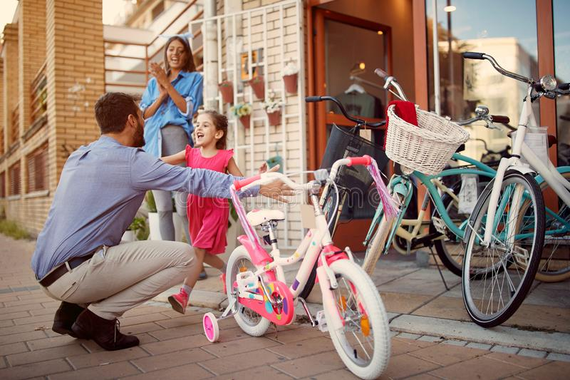 Happy father shopping smiling daughter new bicycle in shop stock photography