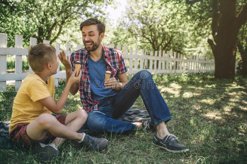 Happy father is sitting besides his son on blanket and smiling to him. Both he and child have ice creams. Guys are stock image
