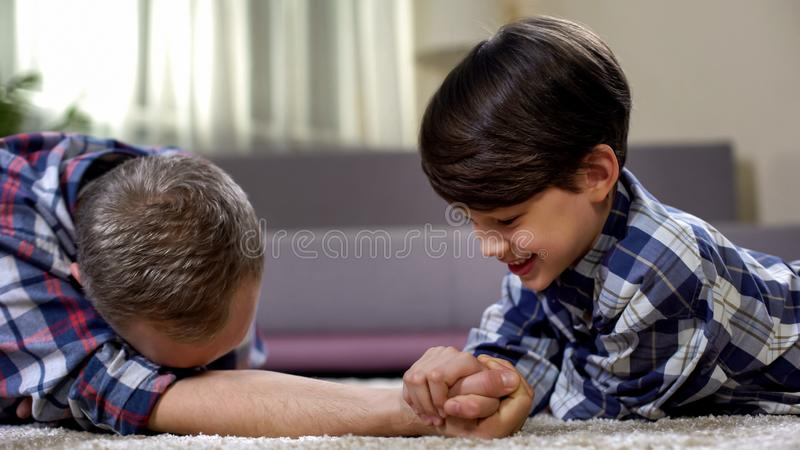 Happy father and son armwrestling on floor, little boy winning, free time. Stock photo royalty free stock images