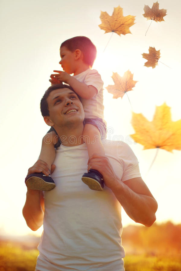 Happy father and son child walking together enjoying sunny autumn park, family on sunset, flying maple leaves stock photo
