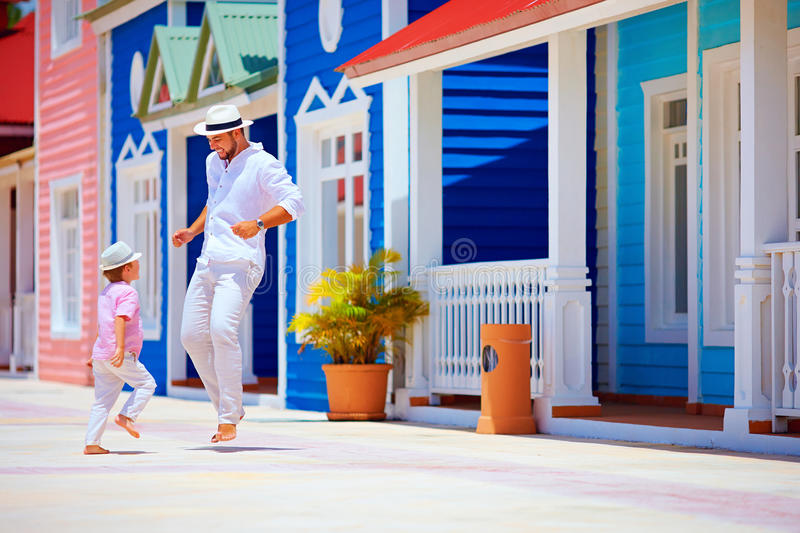 Happy father and son enjoy life, dancing on caribbean village street stock photos