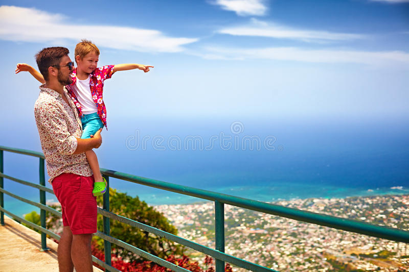 Happy father and son enjoying the fascinating view on Atlantic ocean coastline from observation deck of Pico Isabel de Torres royalty free stock image