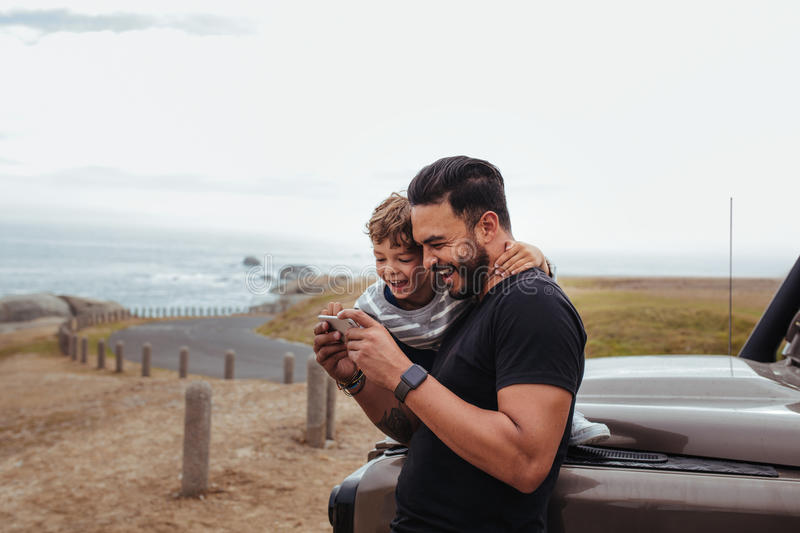 Happy father and son in front of the car using smart phone royalty free stock photography