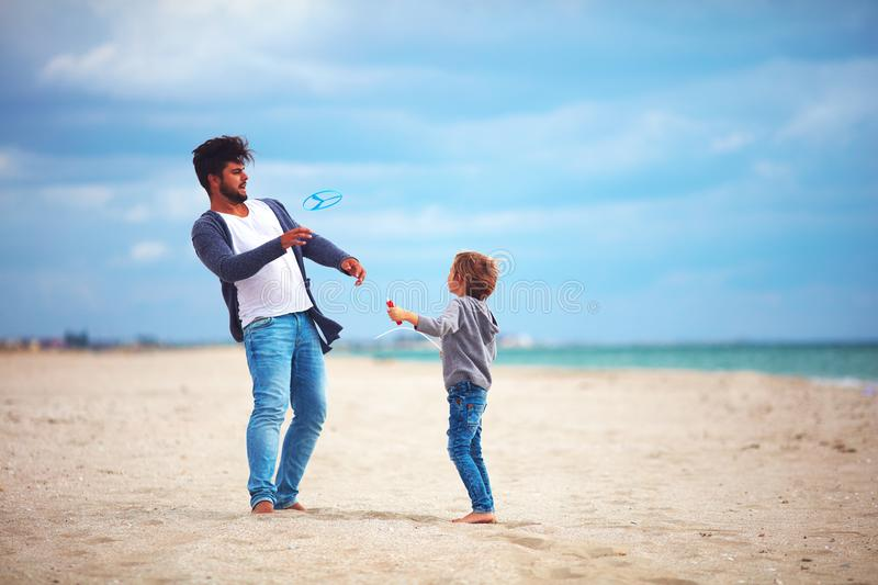 Happy father and son having fun on the beach, playing summer activity games, launching propeller toy in the air royalty free stock photo