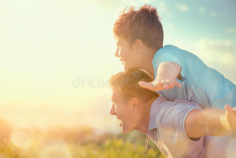 Happy father and son having fun over beautiful sky outdoors. Summer holidays, vacation royalty free stock photos