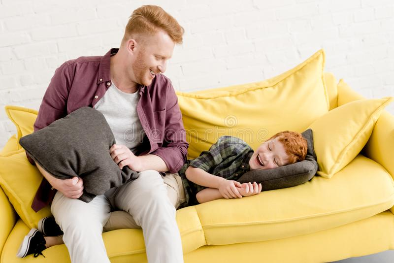 happy father and son having fun with pillows royalty free stock photos
