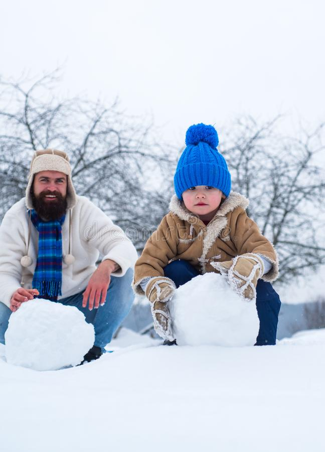 Happy father and son making snowman in the snow. Handmade funny snow man. Best winter game for happy family. royalty free stock photos