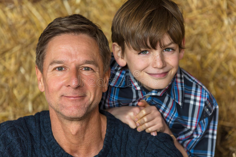 Happy Father Son Man and Boy Smiling on Hay Bales royalty free stock photography