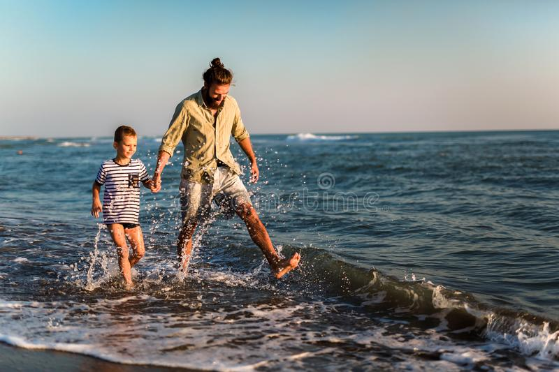 Father and son, man & boy child, running and having fun in the sand and waves of a sunny beach royalty free stock photos