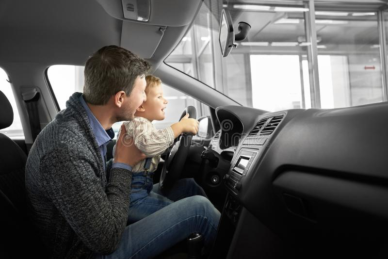 Father and son observing new car cabin in dealership. Happy father and son observing and testing new car in dealership. Parent holding kid on knees, sitting in stock image