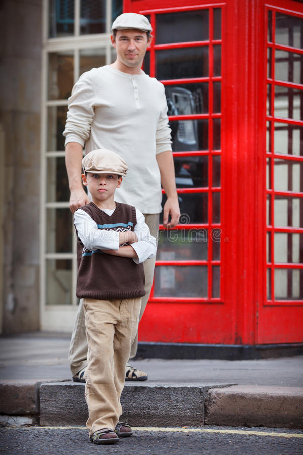Happy father and son outdoors by red phone booth. Happy father and son outdoors in city by red phone booth royalty free stock photo