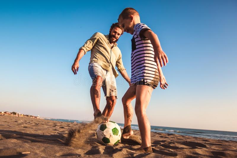 Father and son play soccer or football on the beach having great family time on summer holidays stock image