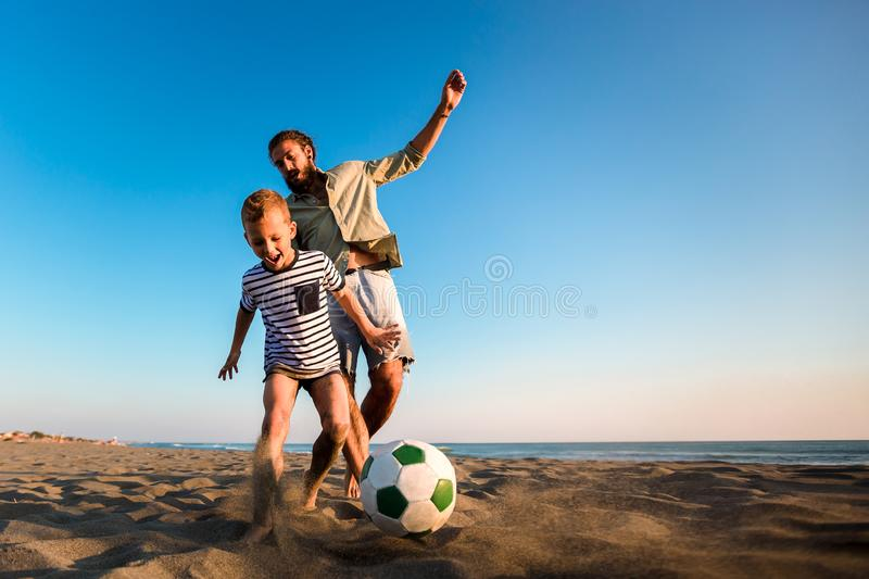 Happy father and son play soccer or football on the beach royalty free stock photography