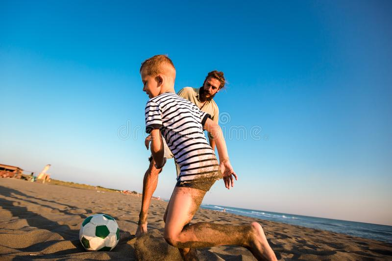 Father and son play soccer or football on the beach having great family time on summer holidays royalty free stock photography