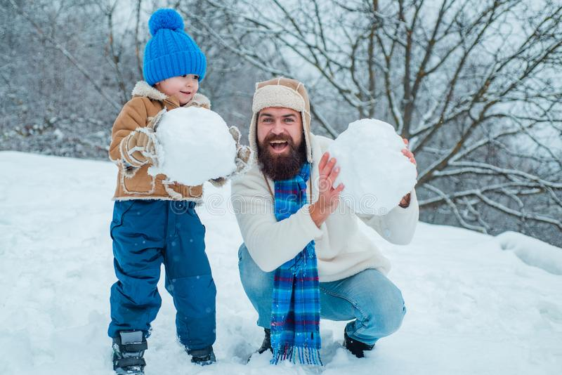 Happy father and son play on winter Christmas time. Happy smiling family on sunny winter day. Concept of friendly family.  royalty free stock image