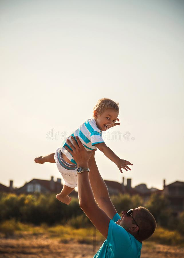 Happy father and son playing together at beach. Father throwing his son in the air stock photography