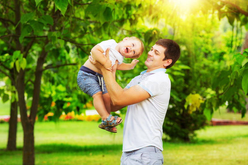 Happy father and son playing together having fun in the green summer park on a warm sunny day. Family and love. stock photography