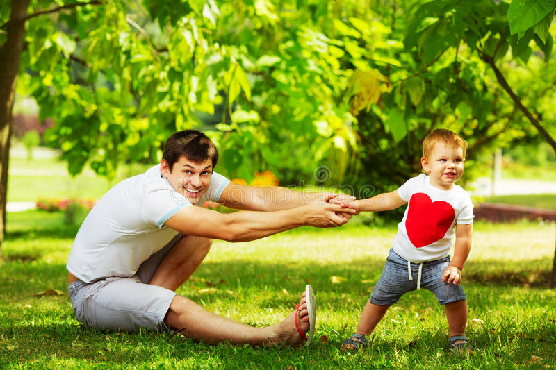 Happy father and son playing together having fun in the green summer park on a warm sunny day. Family and love. stock images