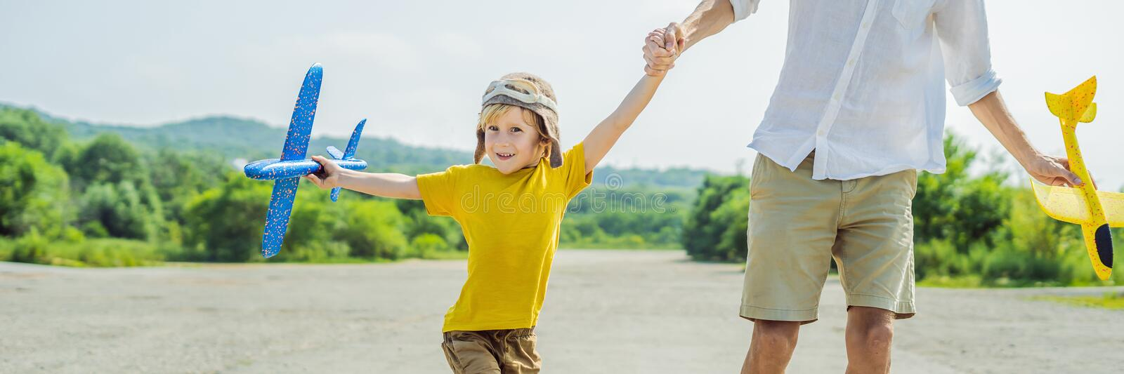 Happy father and son playing with toy airplane against old runway background. Traveling with kids concept BANNER, LONG FORMAT. Happy father and son playing with royalty free stock images