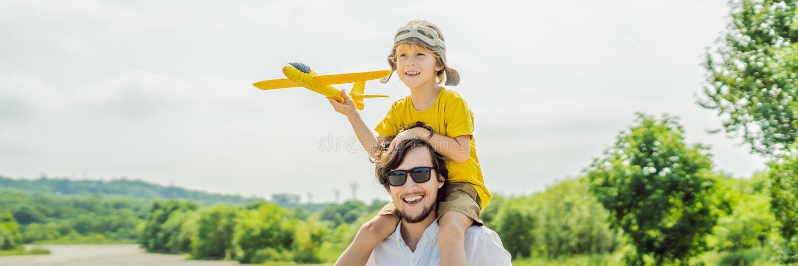 Happy father and son playing with toy airplane against old runway background. Traveling with kids concept BANNER, LONG FORMAT. Happy father and son playing with stock photography
