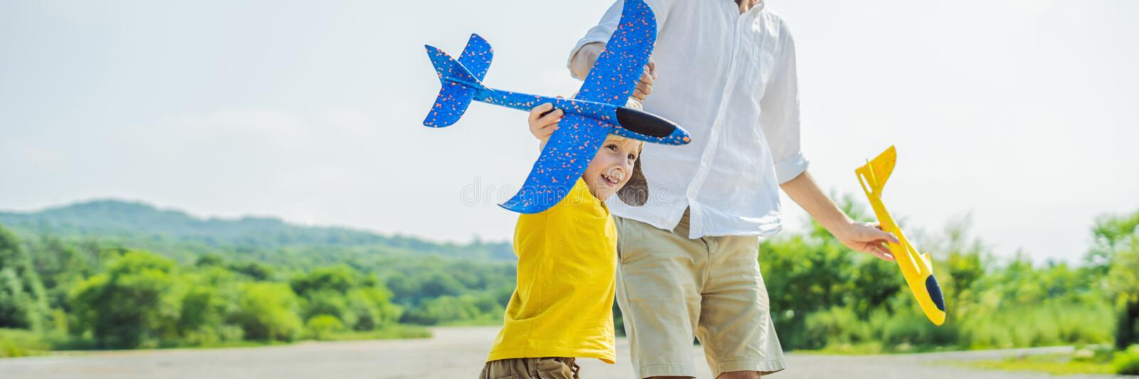 Happy father and son playing with toy airplane against old runway background. Traveling with kids concept BANNER, LONG FORMAT. Happy father and son playing with stock image
