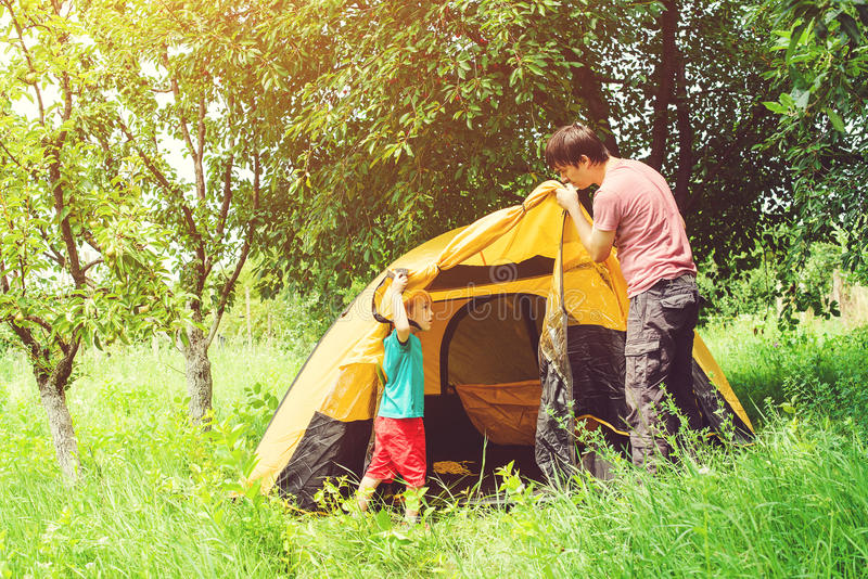 Happy father with son putting up a tent together in woods. royalty free stock image
