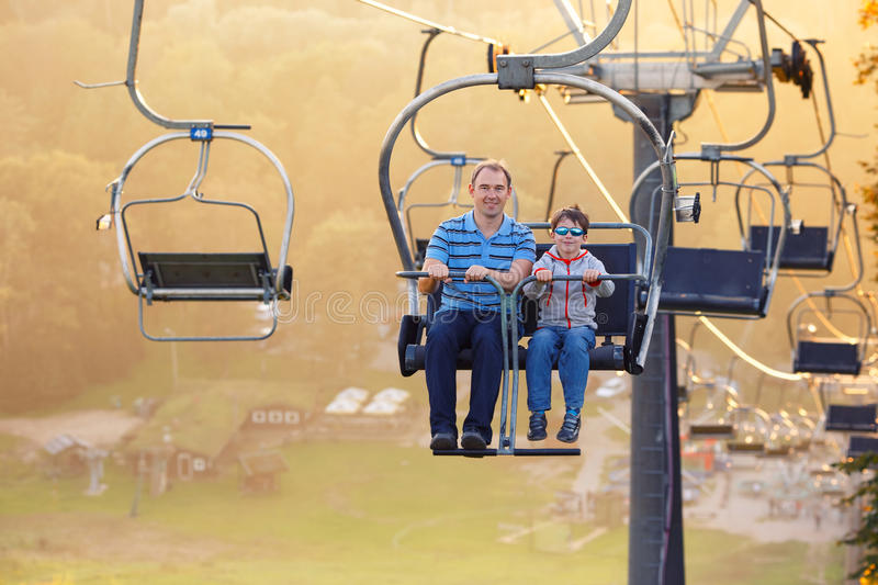 Happy father and son ride chair lift. Happy father and her little son ride chair lift in Sigulda, Latvia, Europe stock photography