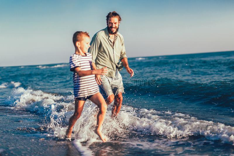 Happy father and son running and having fun in the beach. Happy father and son, men & boy child, running and having fun in the sand and waves of a sunny beach royalty free stock image