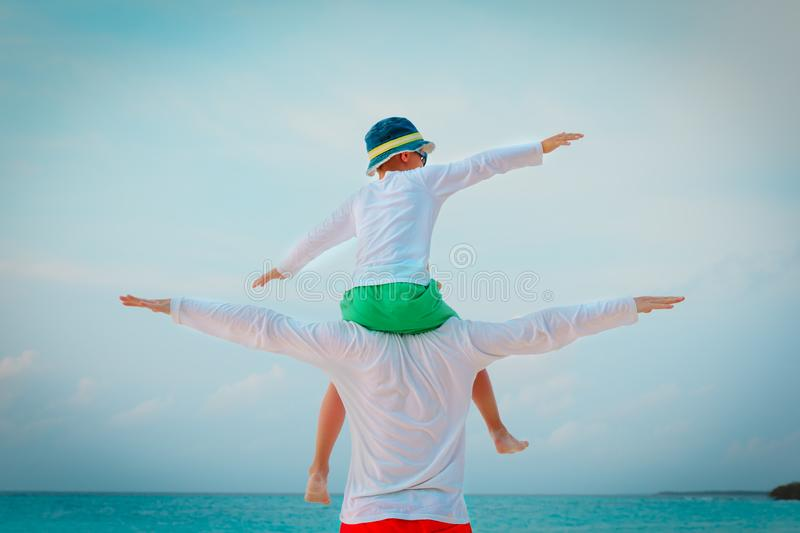 Happy father and son on shoulders play at sky royalty free stock photography