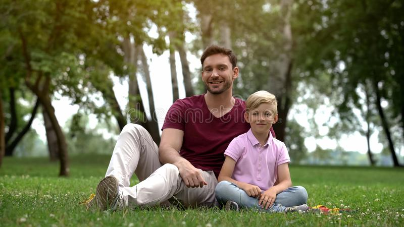 Happy father and son sitting in park, ad of social support for single fathers royalty free stock photos