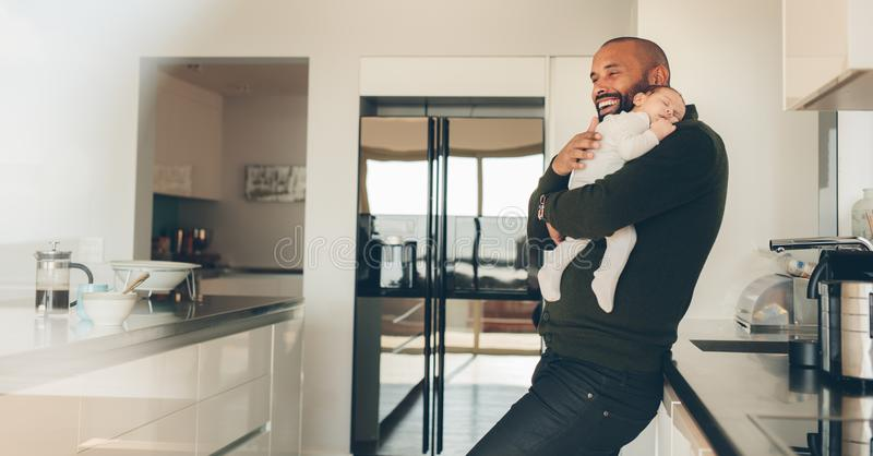 Happy father with son sleeping in his arms in kitchen stock photography