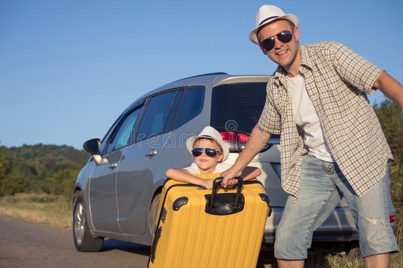 Happy father and son standing near the car at the day time stock image