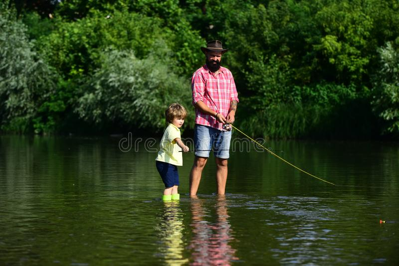 Happy Father and Son together fishing in summer day on the river. Anglers. Happy family concept - father and son stock photography