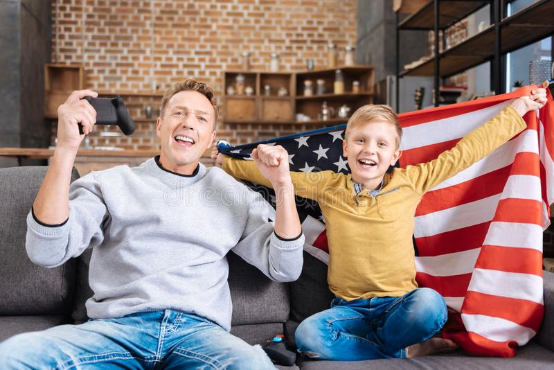 Happy father and son in US flag celebrating on sofa. Joyful celebration. Overjoyed pre-teen boy wrapped in the US flag sitting on the sofa next to his father and stock photo