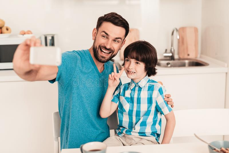 Happy Father and Son Using Smartphone at Home stock photo